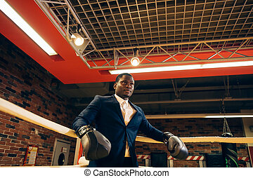 person wearing business suit and boxing gloves.