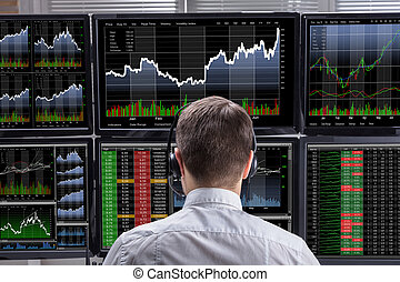 Stock Market Broker Analyzing Graphs On Computer Screens