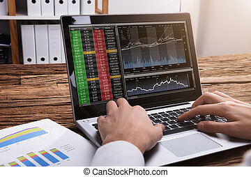 Stock Market Broker Looking At Graphs On Laptop
