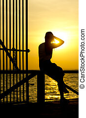 Stock Photo: Profile of a woman silhouette watching sun on the beach at sunset