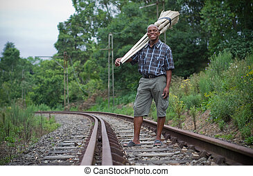 Stock photograph of South African entrepreneur small business broom salesman on railway line