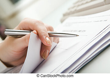 Stock-taking - Close-up of hand holding pen with paper over...
