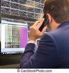 Stock trader looking at computer screens.