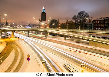 Stockholm Cityhall at night with transportation light trail...