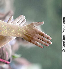 STOCKHOLM, SWEDEN - MAY 22, 2016: Clapping hands covered with yellow color powder in the Color Run Event in Sweden, May 22, 2016