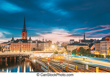 Stockholm, Sweden. Scenic View Of Stockholm Skyline At Summer Sunset. Riddarholm Church And Subway Railway With Train In Blurred Motion
