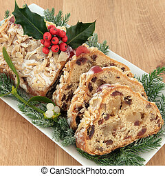 Stollen christmas cake with holly, mistletoe and winter greenery over oak background.