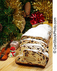Slices of stollen on a wooden board with Christmas themed decorations