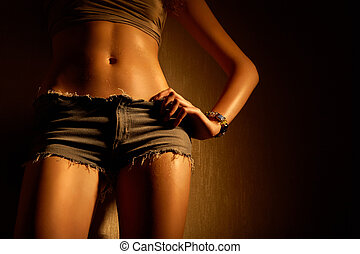 Close up of a harmonous female stomach and hips in jeans shorts