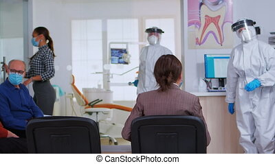 Stomatological doctor with protection suit inviting next patient in dental room for teeth examination during coronavirus. Assistant and dentist doctor wearing overall, face shield, mask, gloves