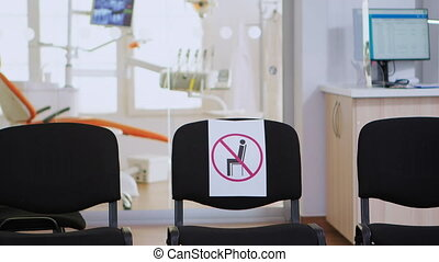 Empty waiting area, stomatology reception with nobody in it with new normal having sign on chair for social distance during covid-19 epidemic. Dental waiting room modern equipped in outbreak time