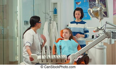 Stomatologist doctor explaining to mother the dental process of intervention for teeth problems of kid, girl showing to affected mass. Orthodontist speaking to child sitting on stomatological chair
