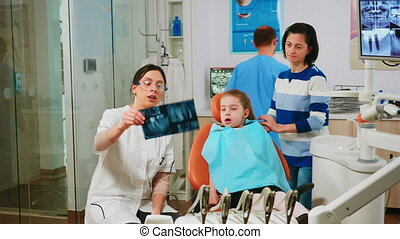 Stomatologist explaining dental treatment holding radiography pointing on affected teeth while man assistant preparing sterilized tools for surgery. Doctor and nurse working in stomatological unit