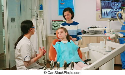 Stomatologist explaining to little girl the cleaning process of teeth while man assistant preparing sterilized tools for examination. Nurse and doctor working together in modern stomatological clinic
