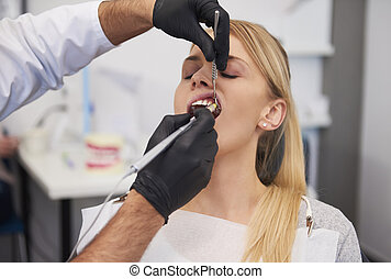 Stomatologist giving woman anesthesia in dentist's clinic