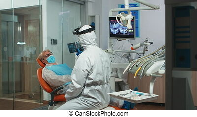 Stomatologist in protective suit asking for patient dental x-ray examining teeth problems during coronavirus pandemic in modern clinic. Medical team wearing coverall, face shield, mask and gloves.
