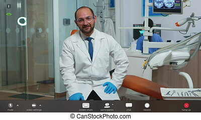 Man stomatologist speaking on video camera sitting on chair in dental clinic. Stomatologist speaking on webcam in stomatological clinic having virtual discussion, footage with software overlay concept