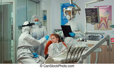 Stomatologist with face shield measuring girl temperature before dental examination during global pandemic. Concept of new normal dentist visit in coronavirus outbreak wearing protective suit.