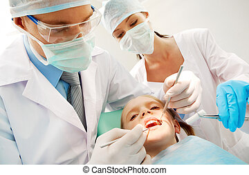 Stomatologists - A dentist and a nurse curing little girl?s...