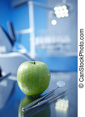 Apple and dental instruments in the foreground