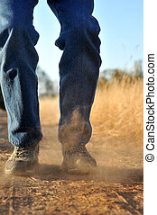 Stomping on Dirt - A person stomps on dirt, causing dust to...