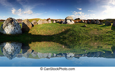 stone age or viking burial site in Denmark. stones reflection in water of historic grave