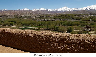 Stone and mud fence in desert grasslands with snow capped...