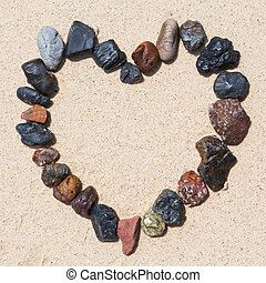 Stone arrangement as heart frame on the beach