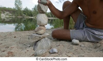 man doing stone piles along the river