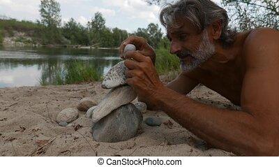 man doing stone piles along the river