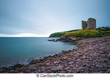 Stone beach and the Minard Castle situated on the Dingle Peninsula in Ireland