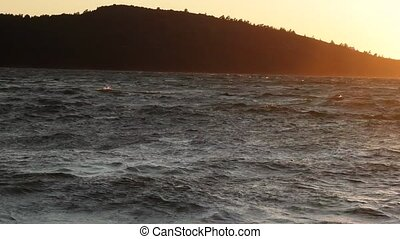 Stone beach, sun path, silhouettes of Islands, sunset. Romantic seaside vacation. Camera in surf, contour