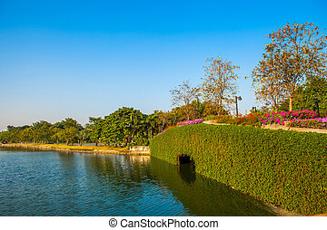 Stone Bridge in a park with lake on blue sky
