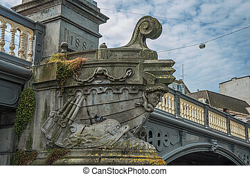 Stone bridge over canal decorated by sculpture of ship's bow and sunny blue sky in Amsterdam.