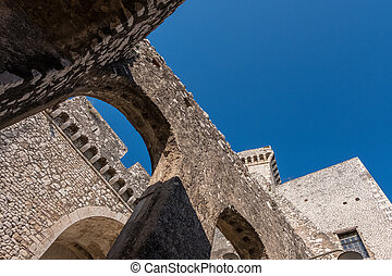 Stone castle architecture with blue sky background.