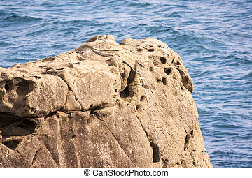 Stone cliff on the sea shore at cloudy day