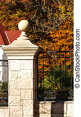 Stone Column on Black Iron Fence in Autumn