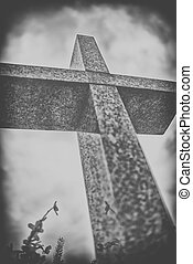 stone cross against dramatic cloudy sky, black and white