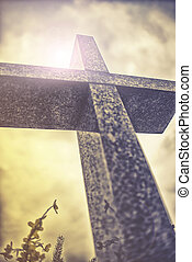 stone cross against dramatic cloudy sky, vintage effect