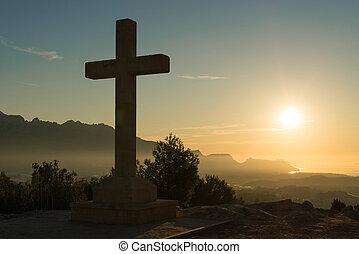 Stone cross - Christian stone cross under the warm light of...