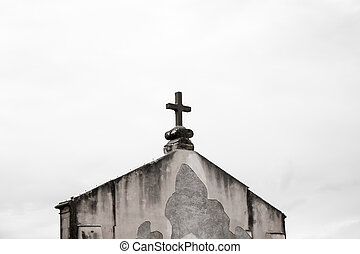 Stone cross on the roof of a church seen from a distance