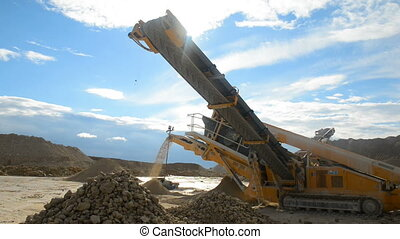 Stone crusher at the quarry - Backlit medium shot of machine...