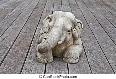 Stone elephant sculpture on a wood board floor