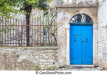 Stone facade with a blue entrance door of an old house in Rovinj, Croatia, Europe.