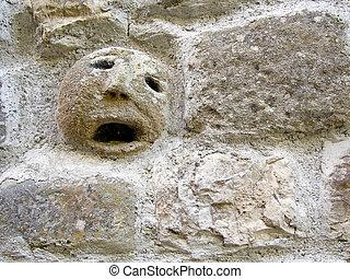 Stone face, faccione, in wall. Italy.