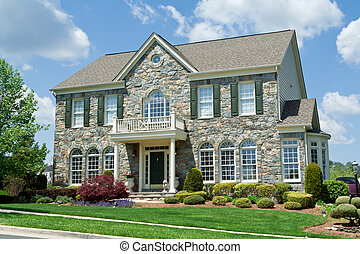 Well landscaped stone single family house. Home is a center hall colonial in suburban Maryland, United States.