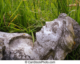A fallen stone figure lays in the grass of a cemetery.