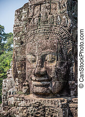 Stone head on towers of Bayon temple in Angkor Thom, Cambodia. South East Asia. Tradition, Culture and Religion.