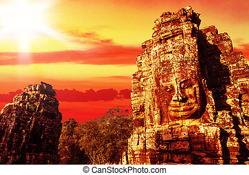 Stone heads - Stone head on towers of Bayon temple at sunset