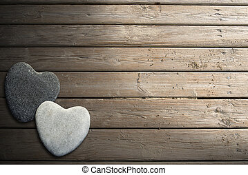 Stone Hearts on Wooden Boardwalk with Sand - Two hearts of...